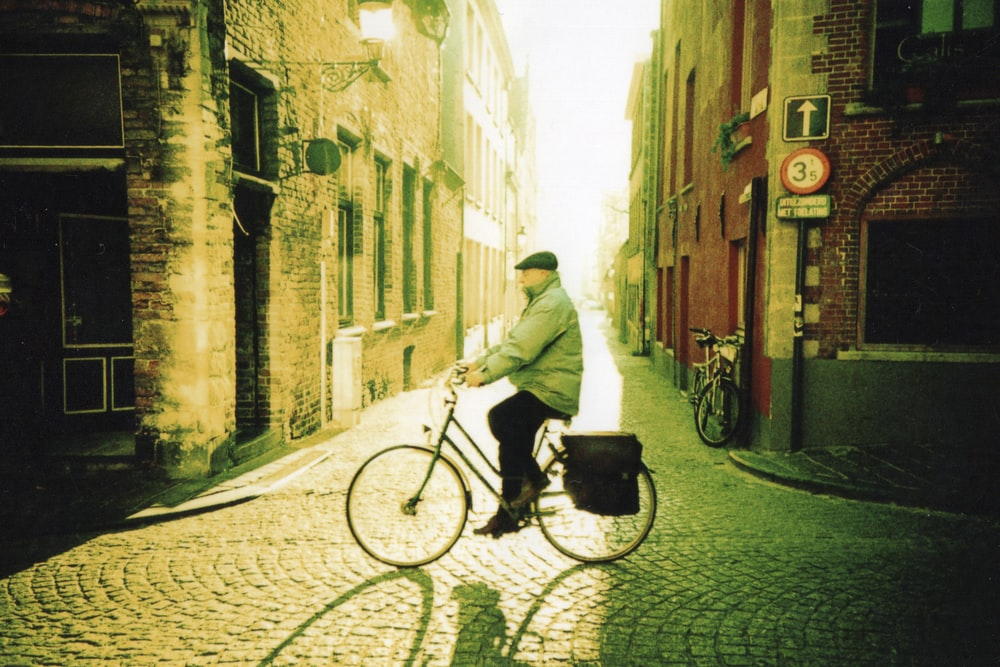 man in white hoodie riding on bicycle on street during daytime