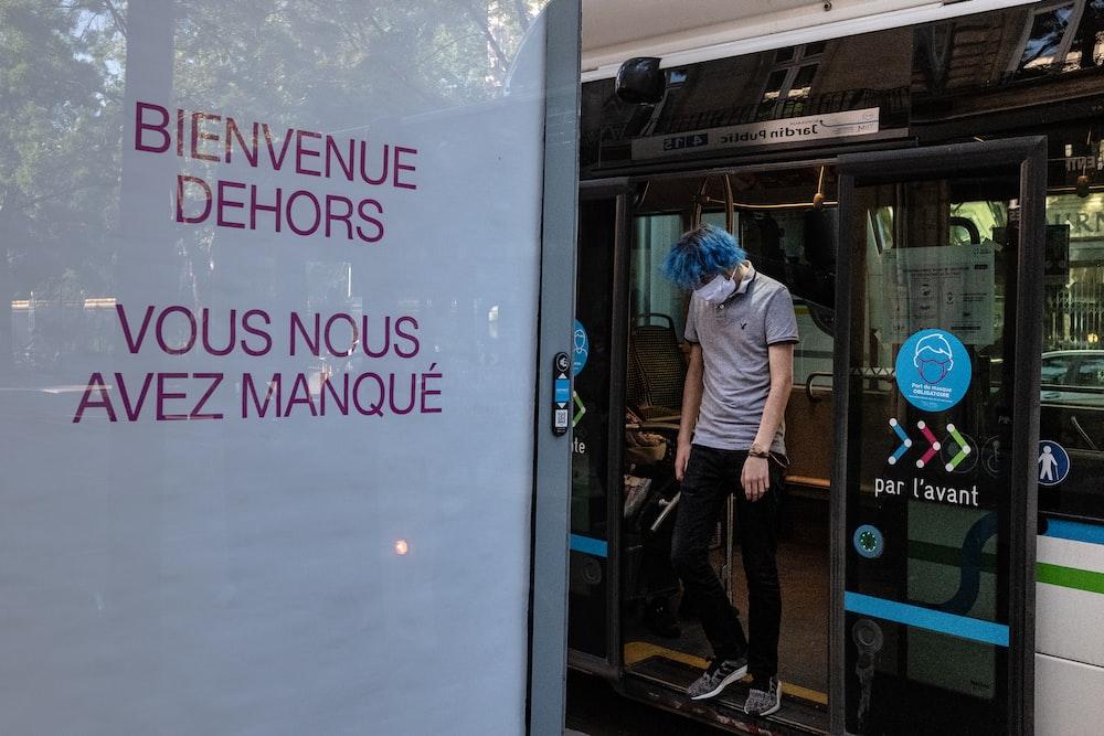 man in blue dress shirt standing beside glass door