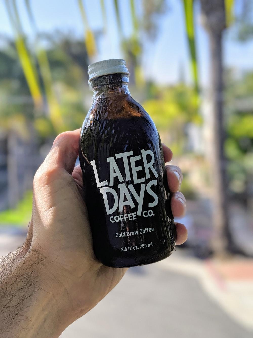 person holding black and white coca cola zero bottle