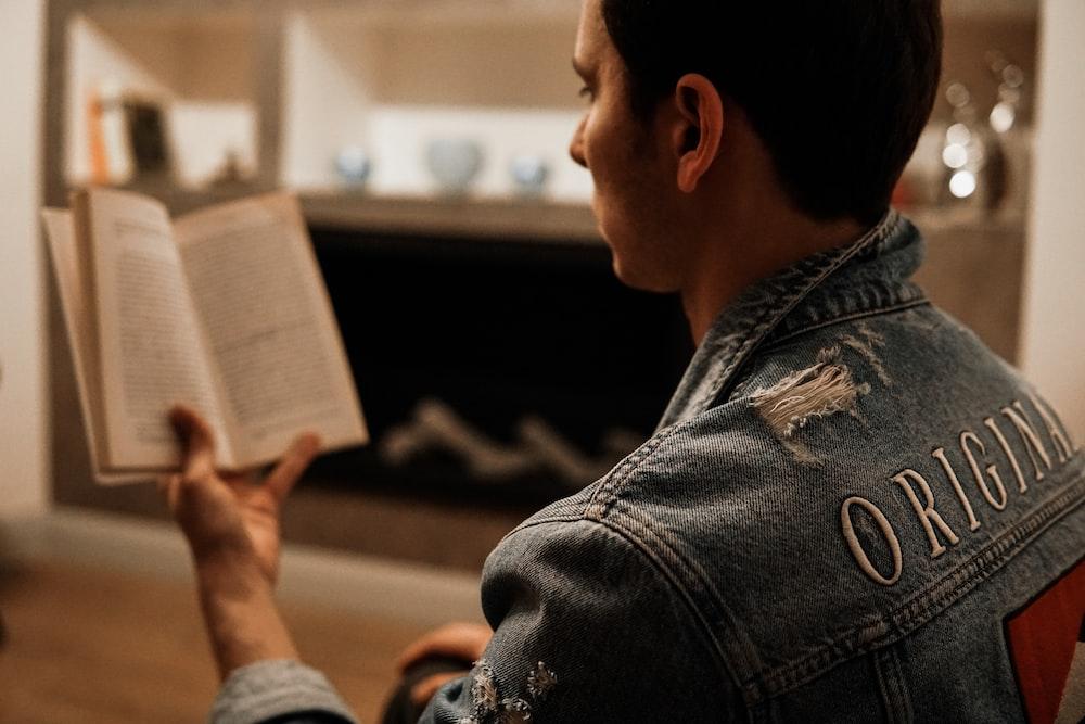 man in blue denim jacket reading book