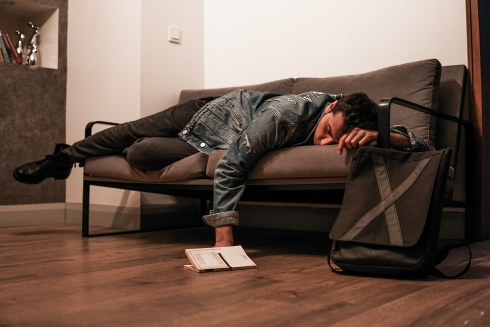 man in black jacket and blue denim jeans lying on brown leather couch