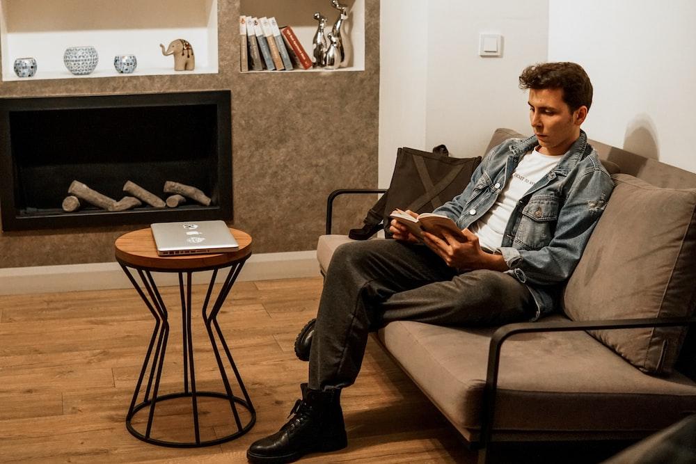 man in blue denim jacket and black pants sitting on black sofa chair