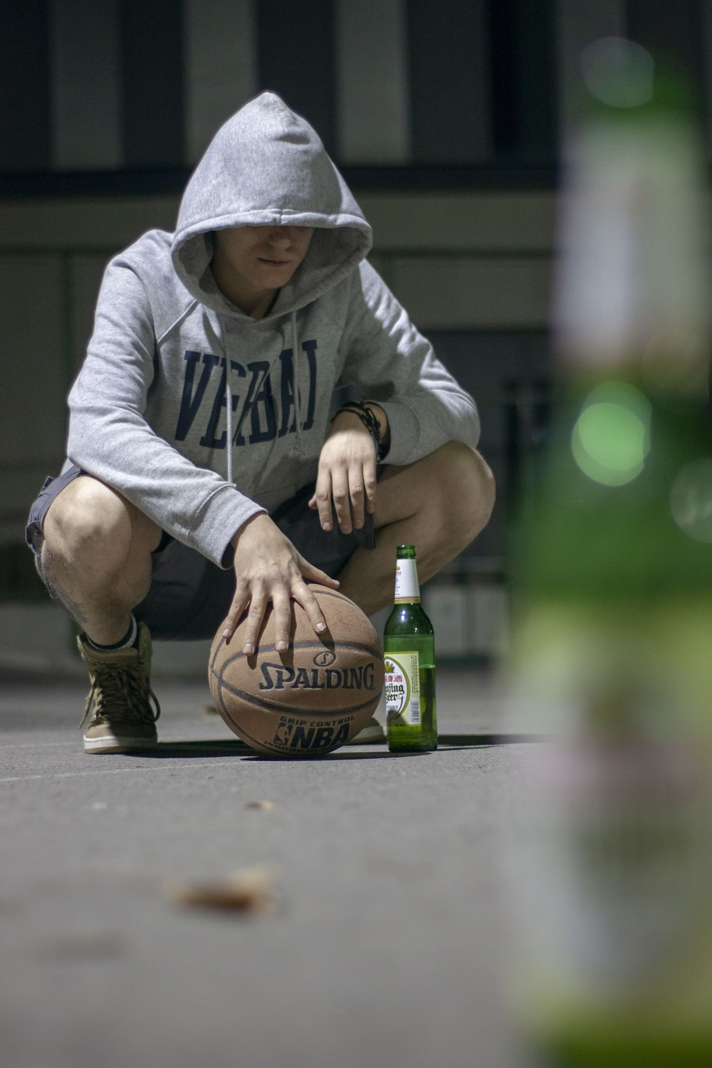 man in gray hoodie holding brown basketball