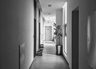 grayscale photo of hallway with white walls