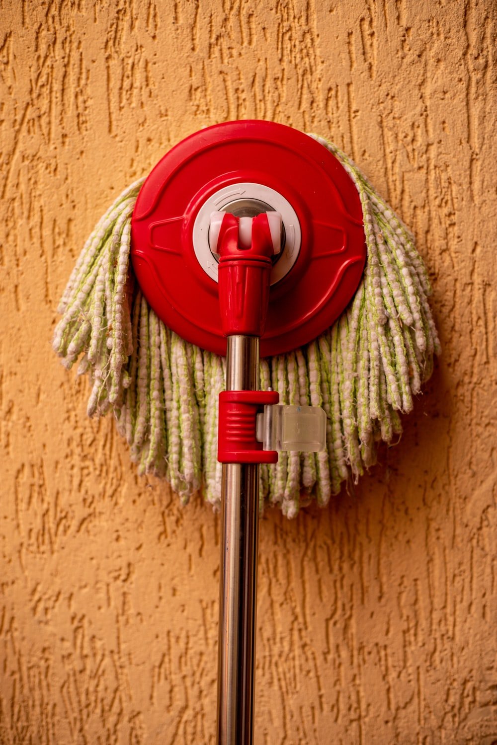 red and silver mop on yellow textile