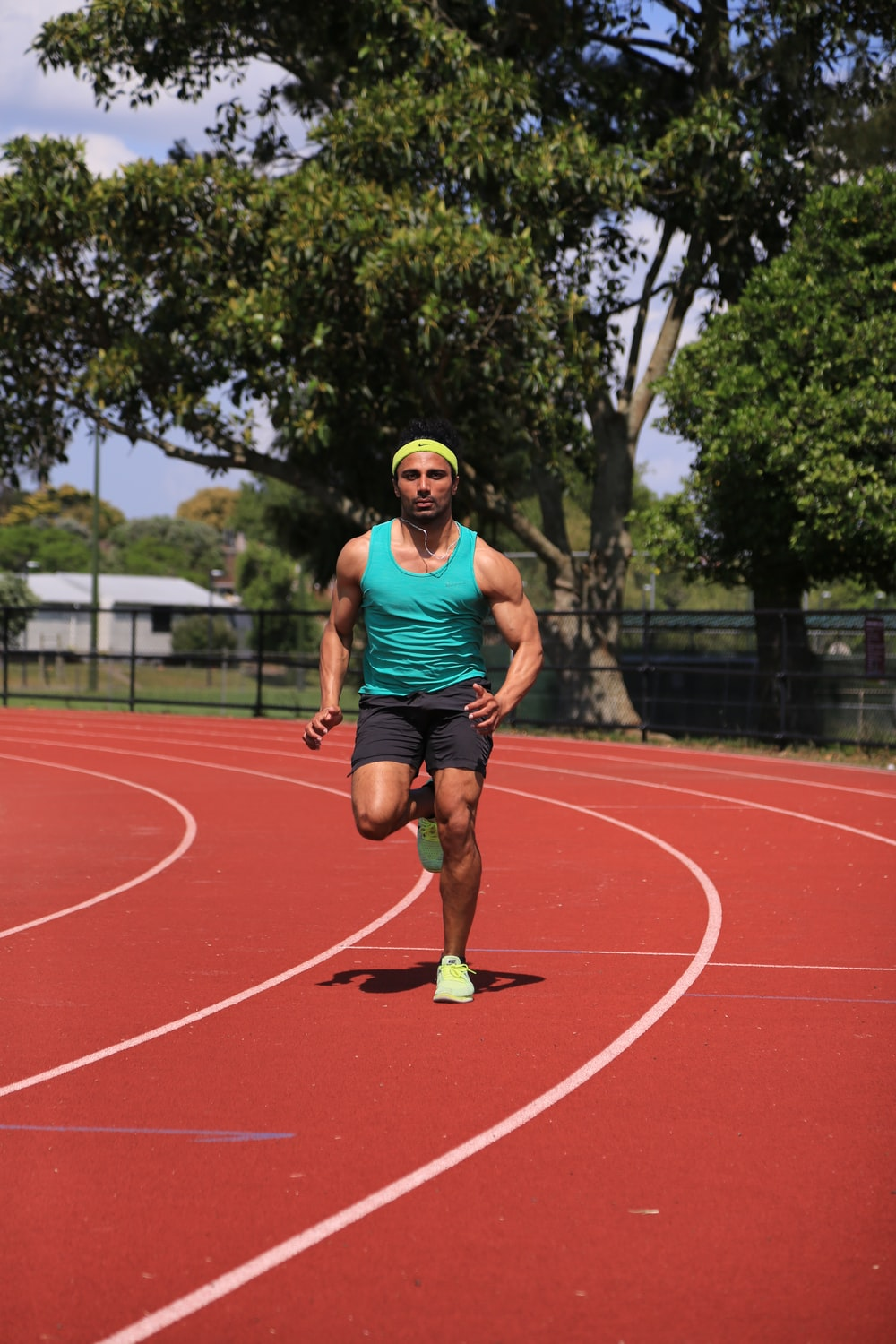 man in green tank top running on track field during daytime