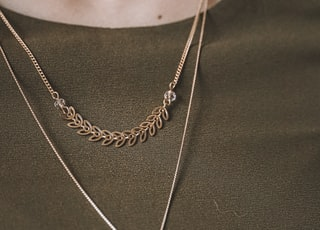 person wearing silver necklace with silver pendant