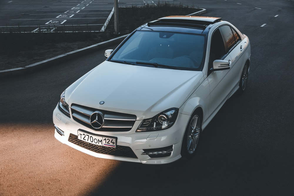 white mercedes benz coupe on road during daytime