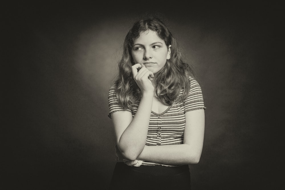 woman in stripe shirt covering her mouth with her hand