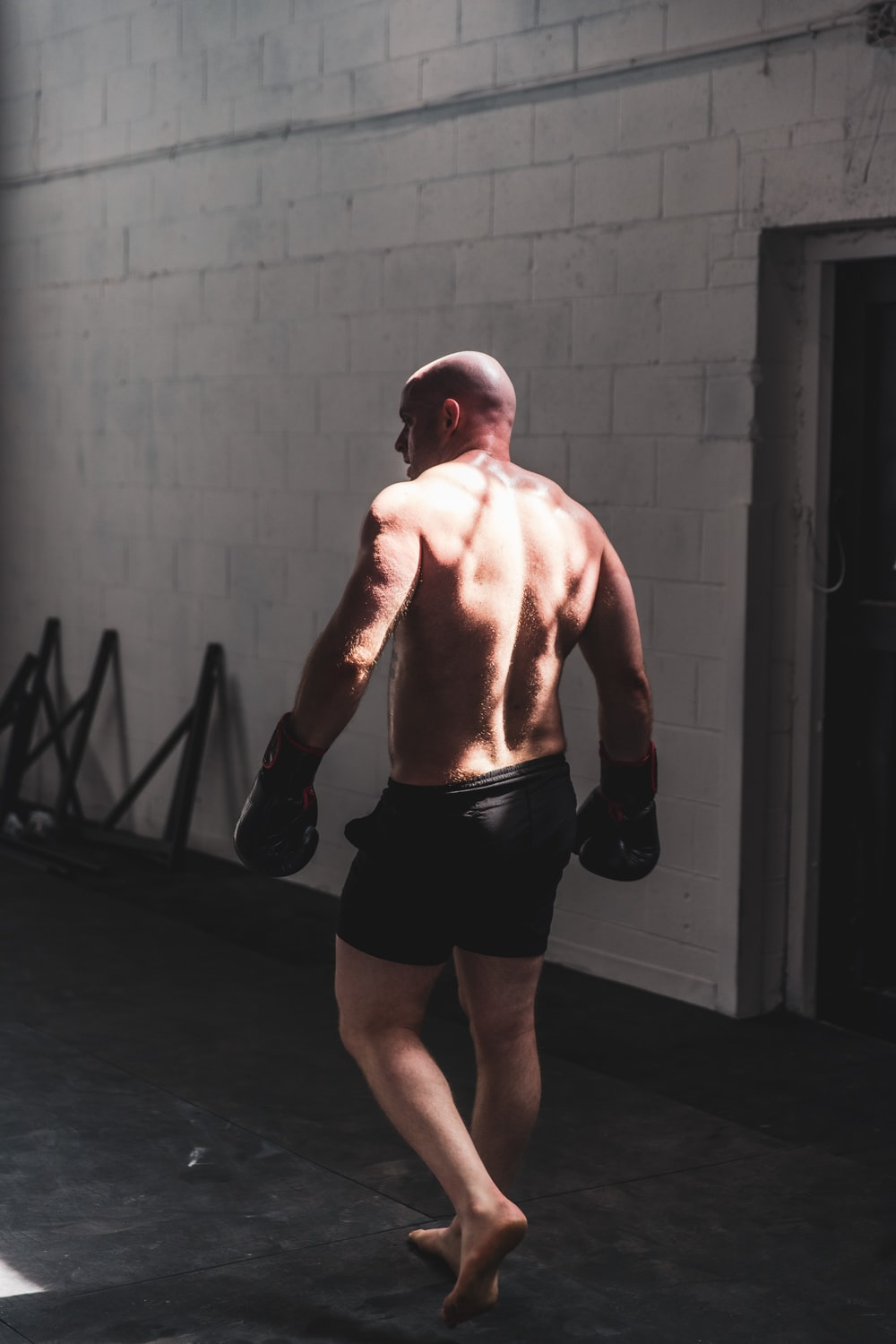 topless man in black shorts standing near gray wall