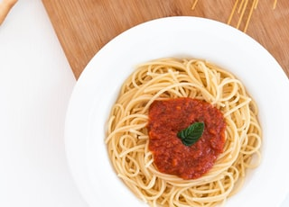 white ceramic bowl with pasta and red tomato on brown wooden table