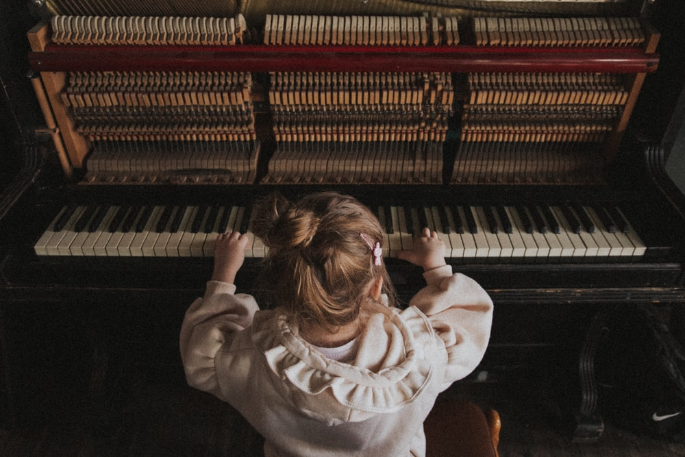 girl in white sweater playing piano