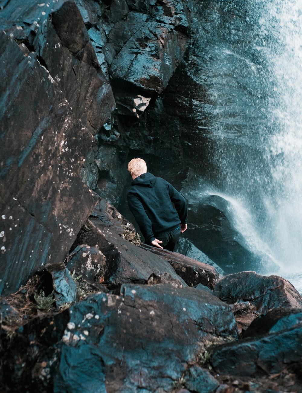 man in black jacket sitting on rock near water falls during daytime