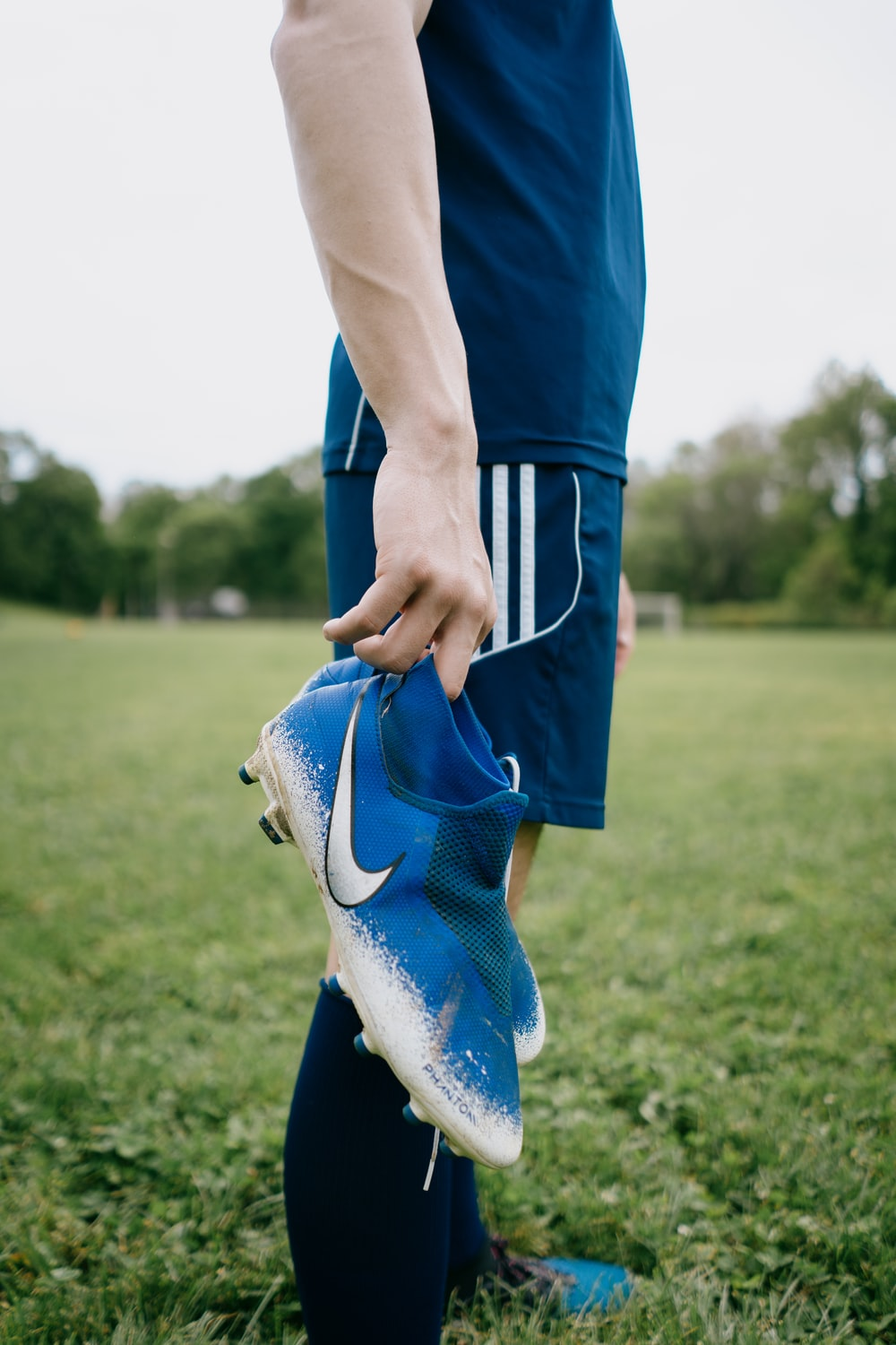 person in blue pants and white nike sneakers
