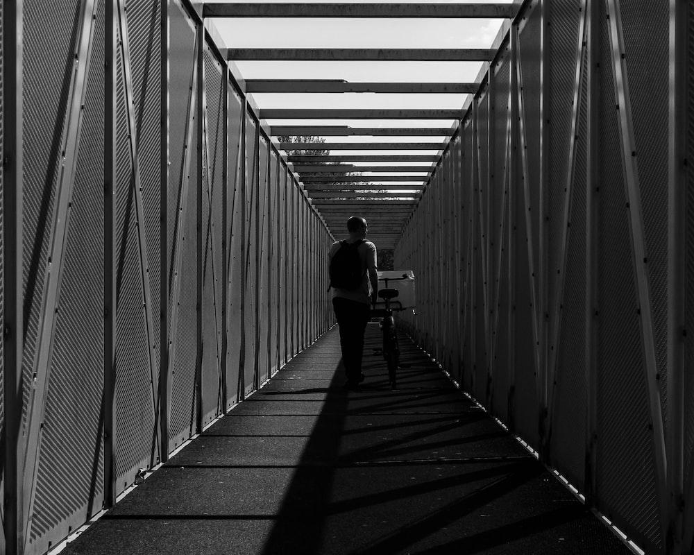 grayscale photo of man walking on the hallway