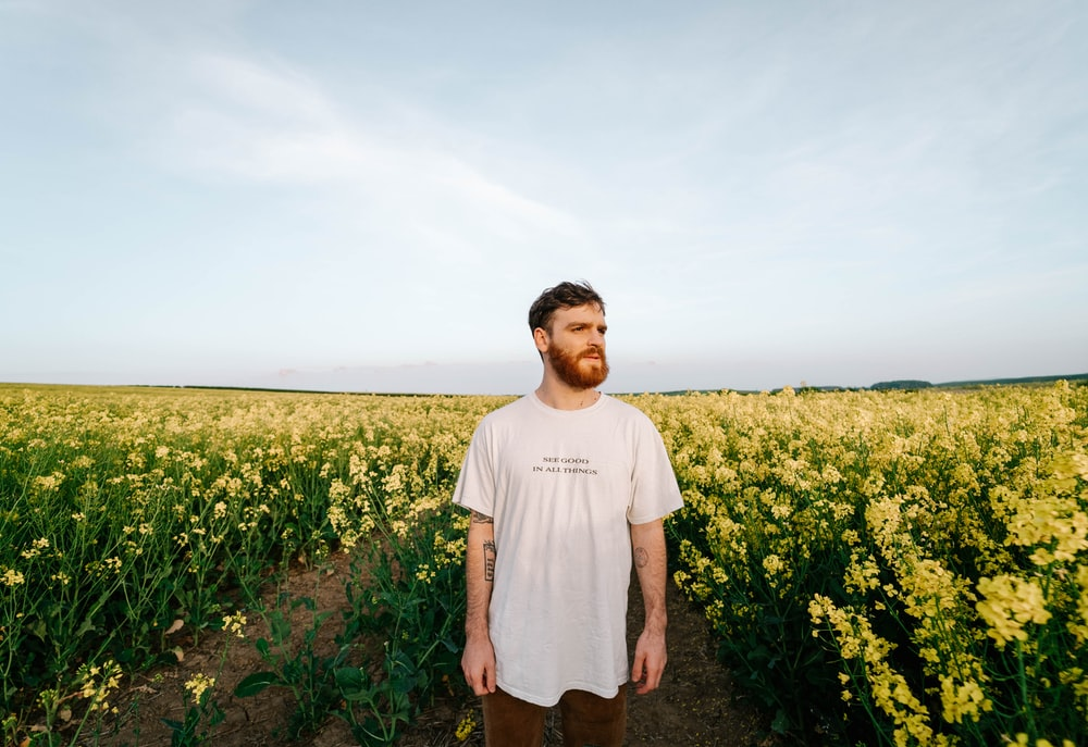 man in white crew neck t-shirt standing on yellow flower field during daytime