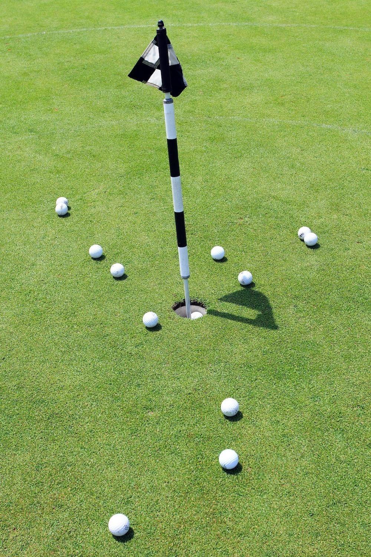 white golf balls on green grass field during daytime