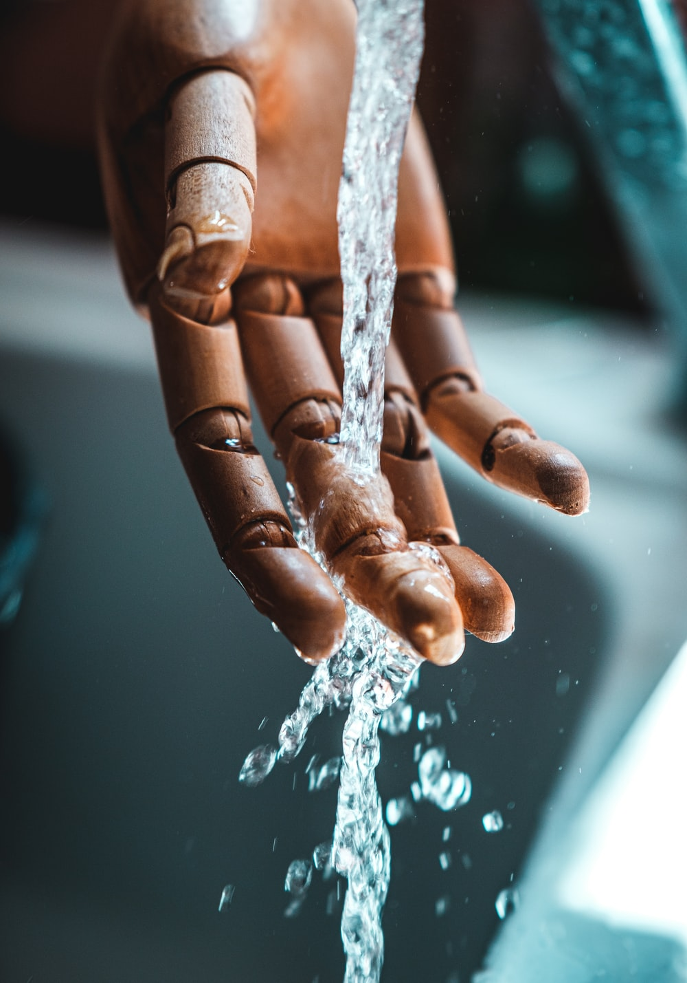 person in brown gloves with water