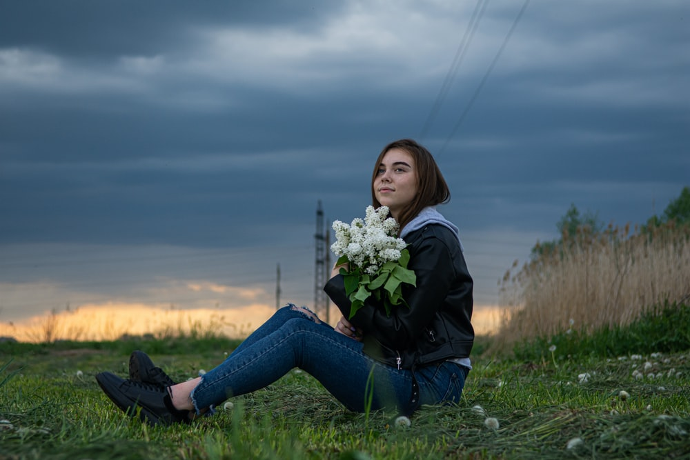 woman in black jacket and blue denim jeans sitting on green grass field holding white flowers