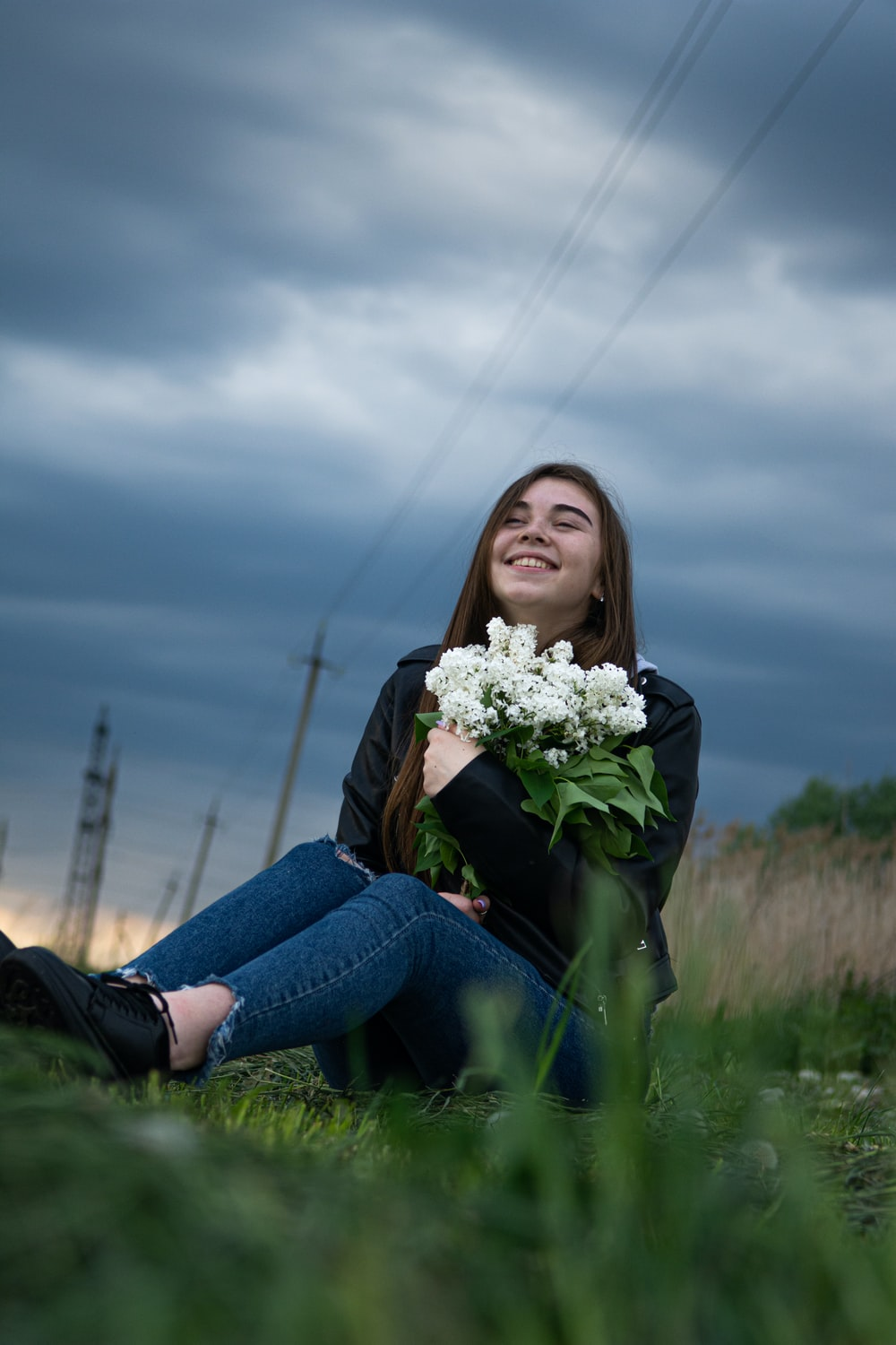 woman in blue denim jeans holding white flowers