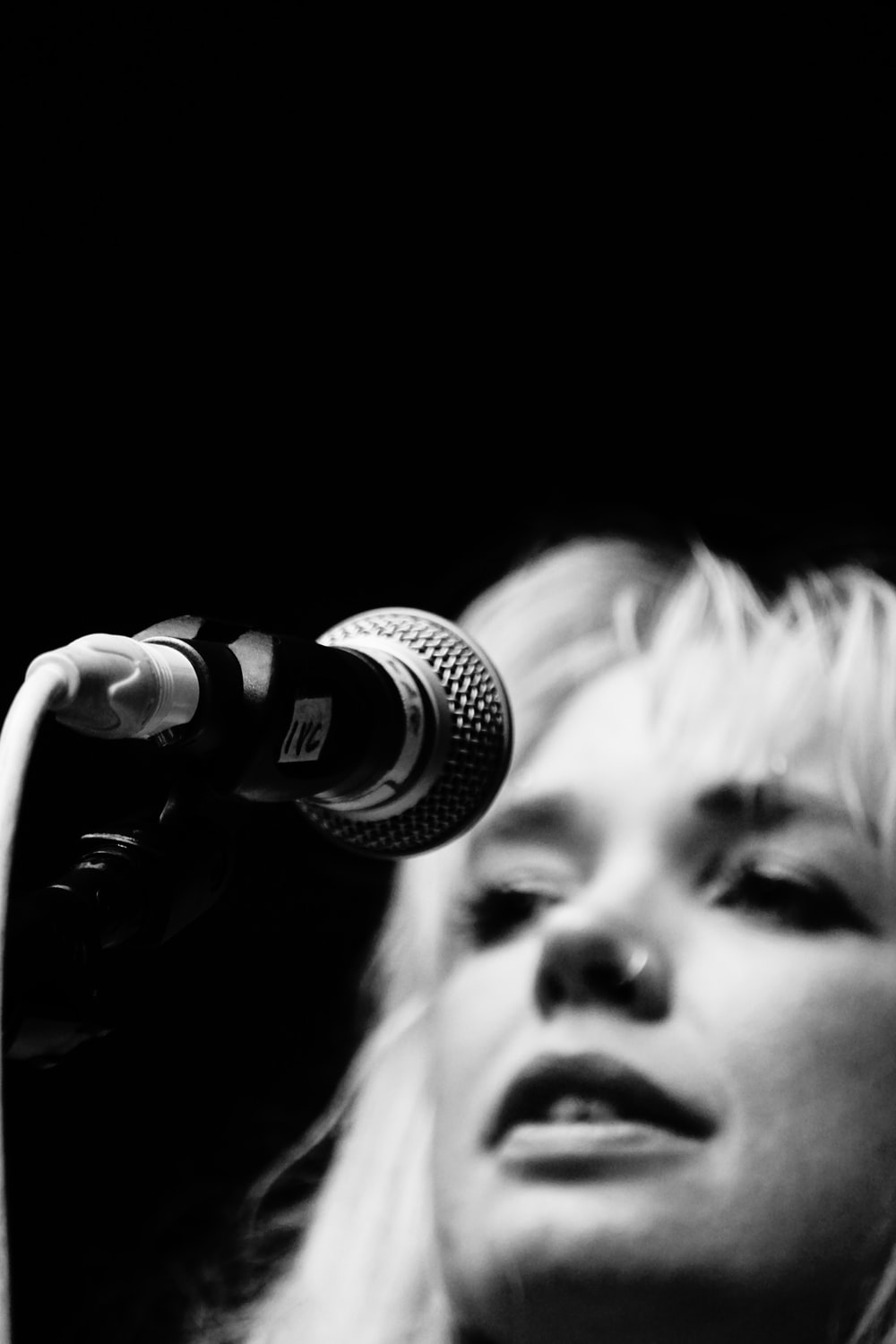 grayscale photo of woman singing