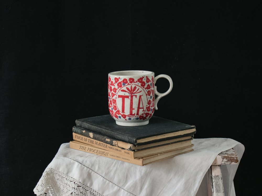 white and red ceramic mug on brown book