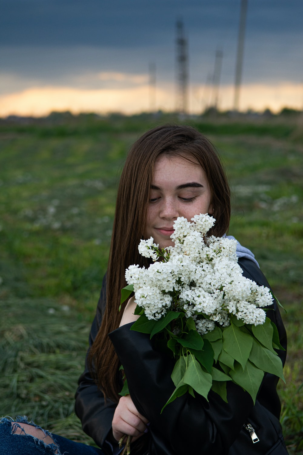 woman in blue long sleeve shirt holding white flowers