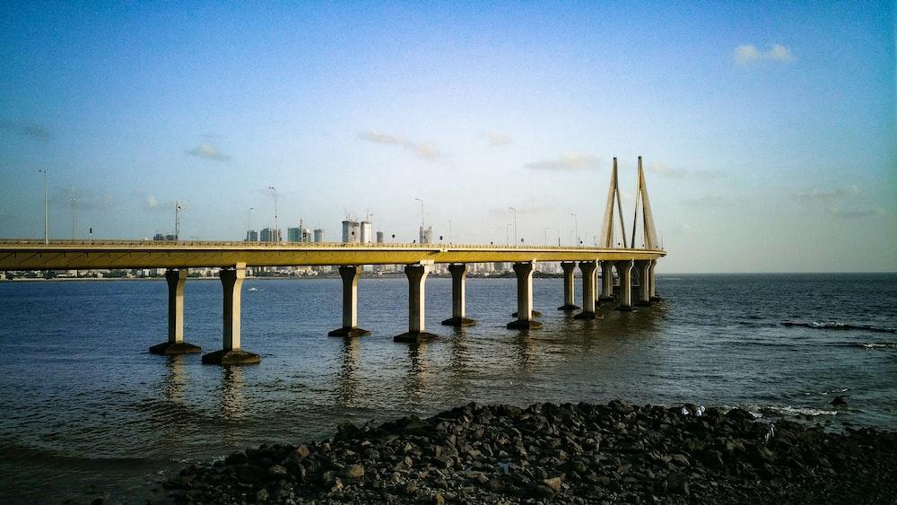 white concrete bridge over the sea during daytime