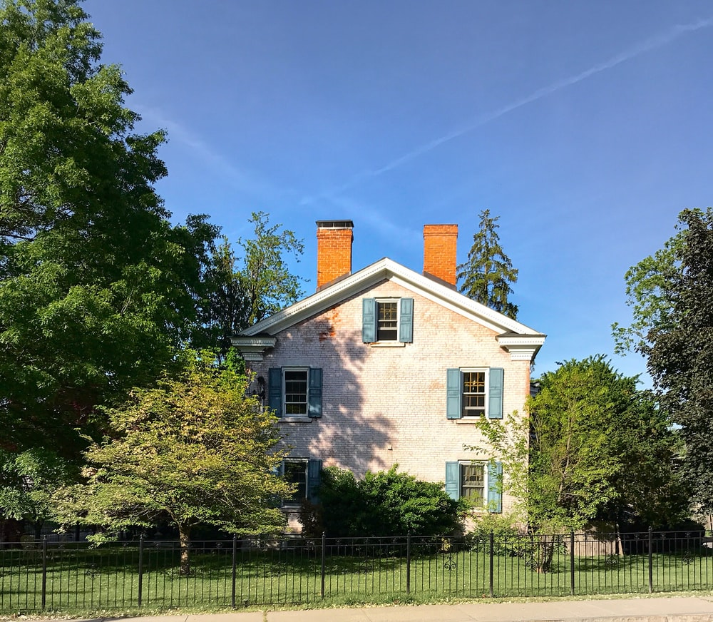 white and brown house near green trees under blue sky during daytime