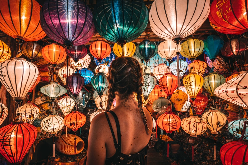 woman in black tank top standing near blue and red paper lanterns