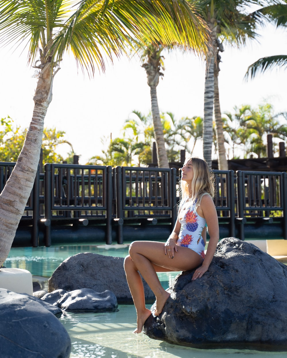 woman in white and pink floral bikini sitting on rock near palm tree during daytime