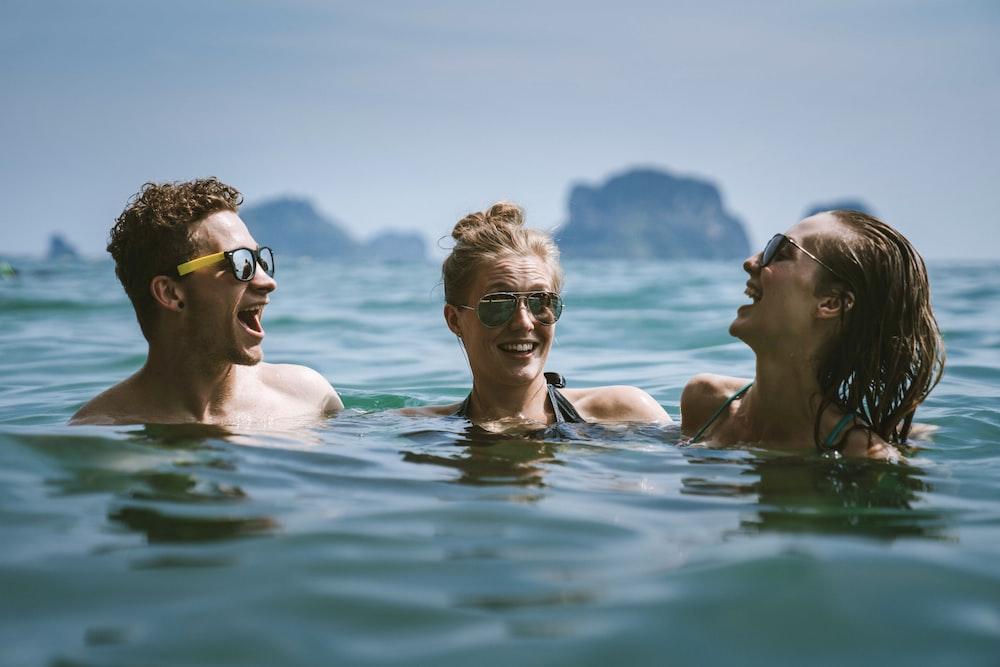 3 women in swimming pool during daytime