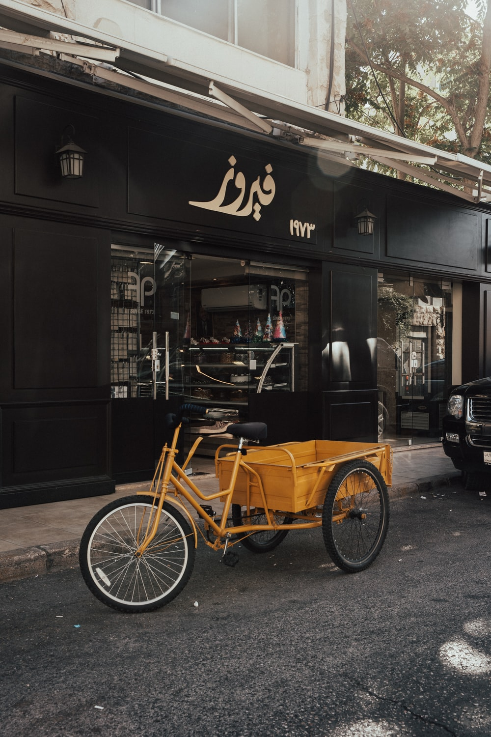black and brown trike parked beside brown wooden store during daytime