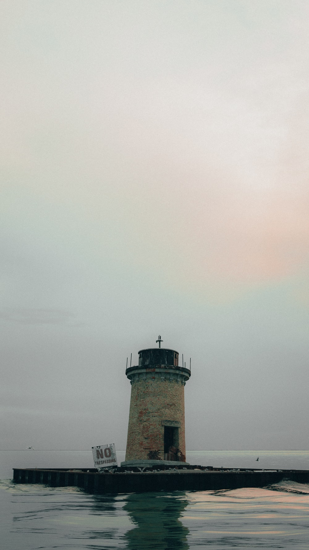 brown and white lighthouse under white clouds