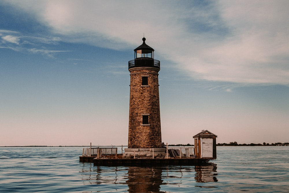 brown and white concrete lighthouse near body of water during daytime