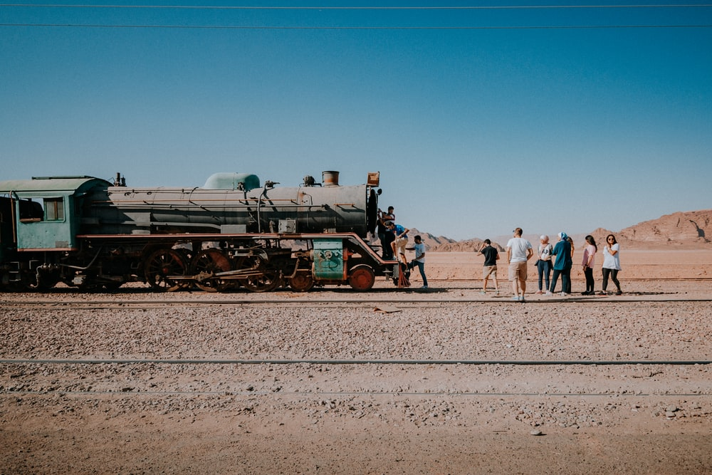 people standing near green and black train under blue sky during daytime