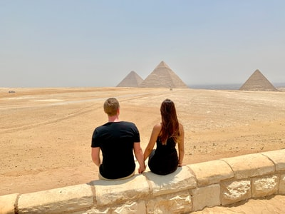 man and woman sitting on concrete wall during daytime cairo zoom background