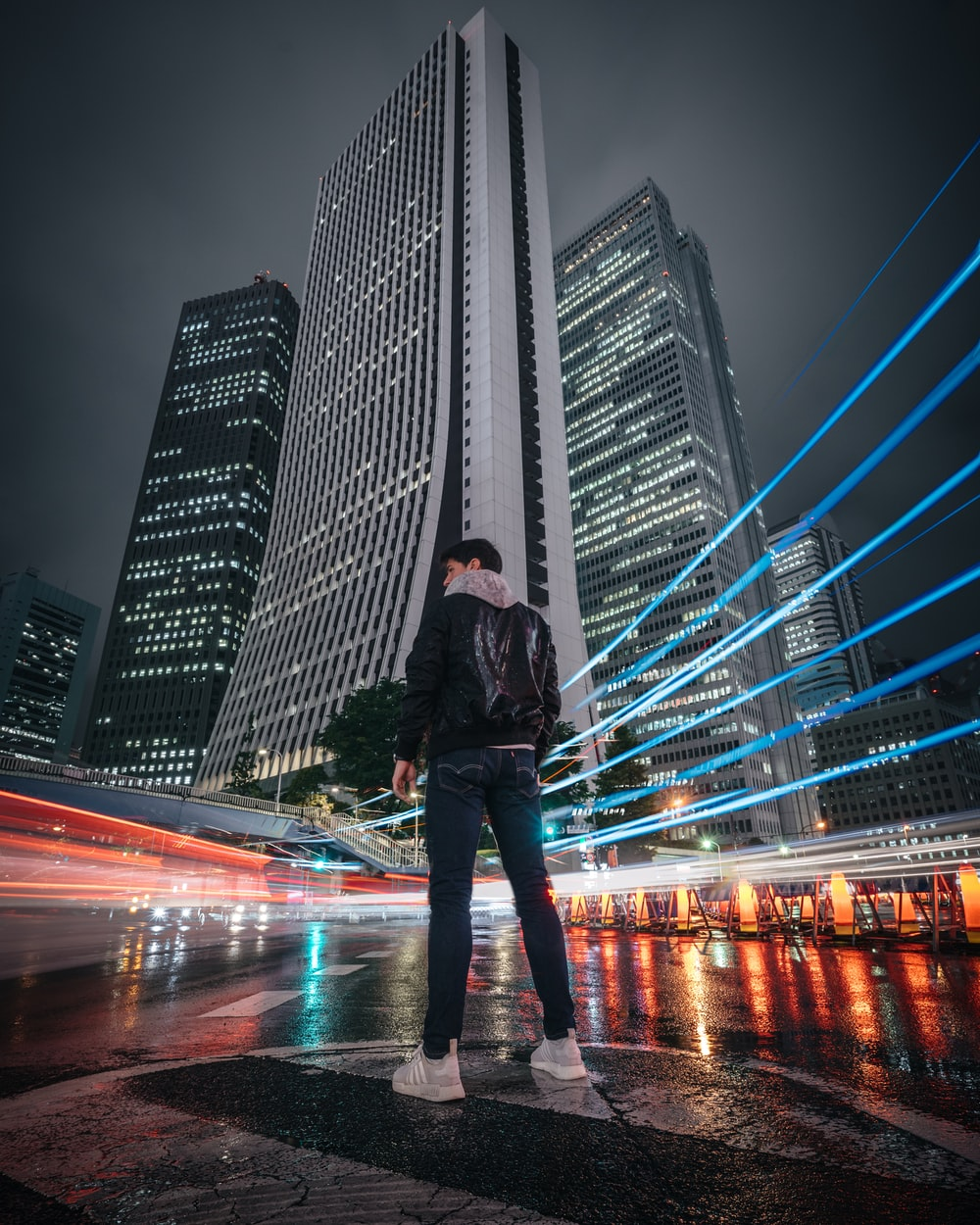 man in black jacket and blue denim jeans standing on road during night time