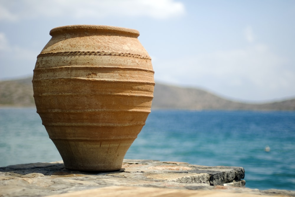 brown clay pot on white sand near body of water during daytime