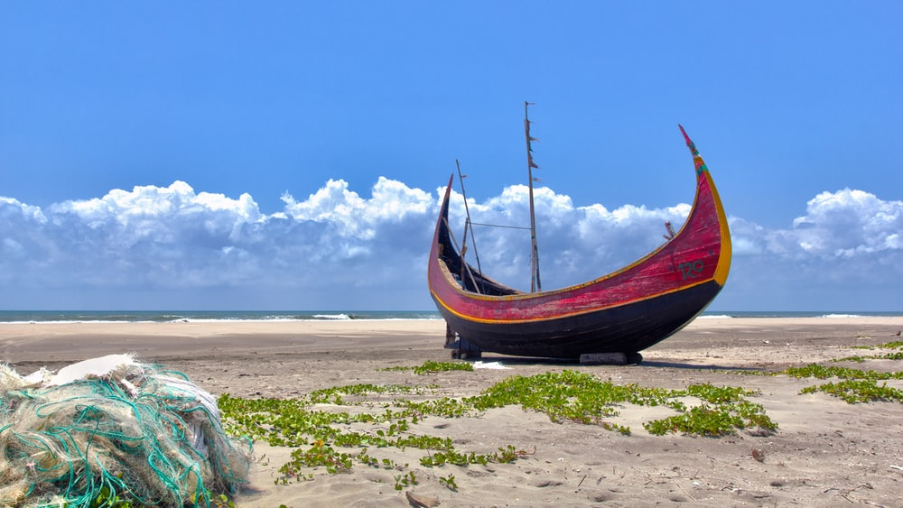 brown boat on white sand during daytime