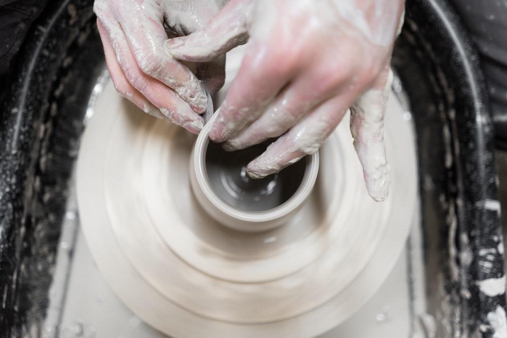 person holding round white ceramic plate