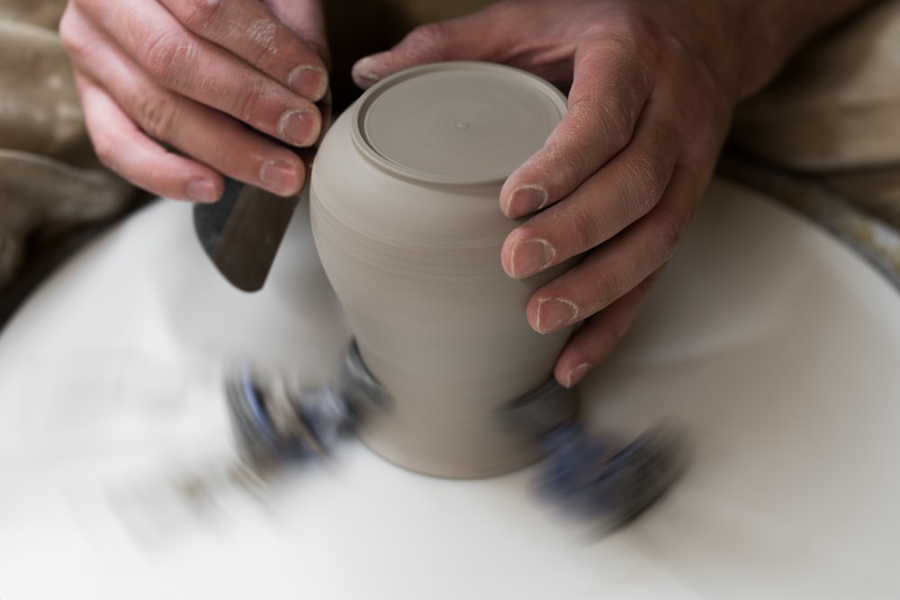 person pouring white liquid on white ceramic cup