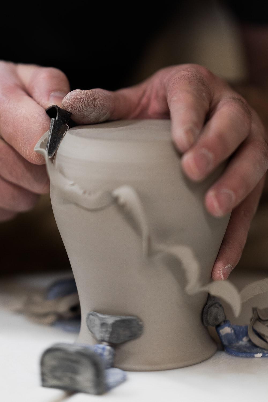 person holding white ceramic vase