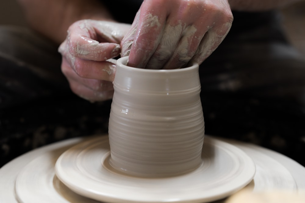 person holding round white ceramic bowl