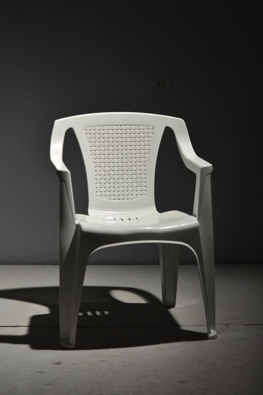 white plastic armchair on white floor