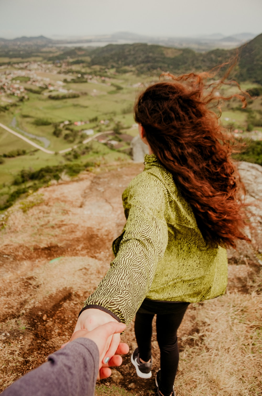 woman in green knit sweater and black skirt sitting on brown rock during daytime