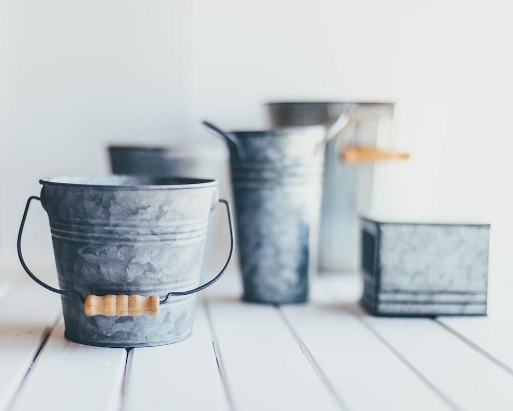 gray steel bucket on brown wooden bucket