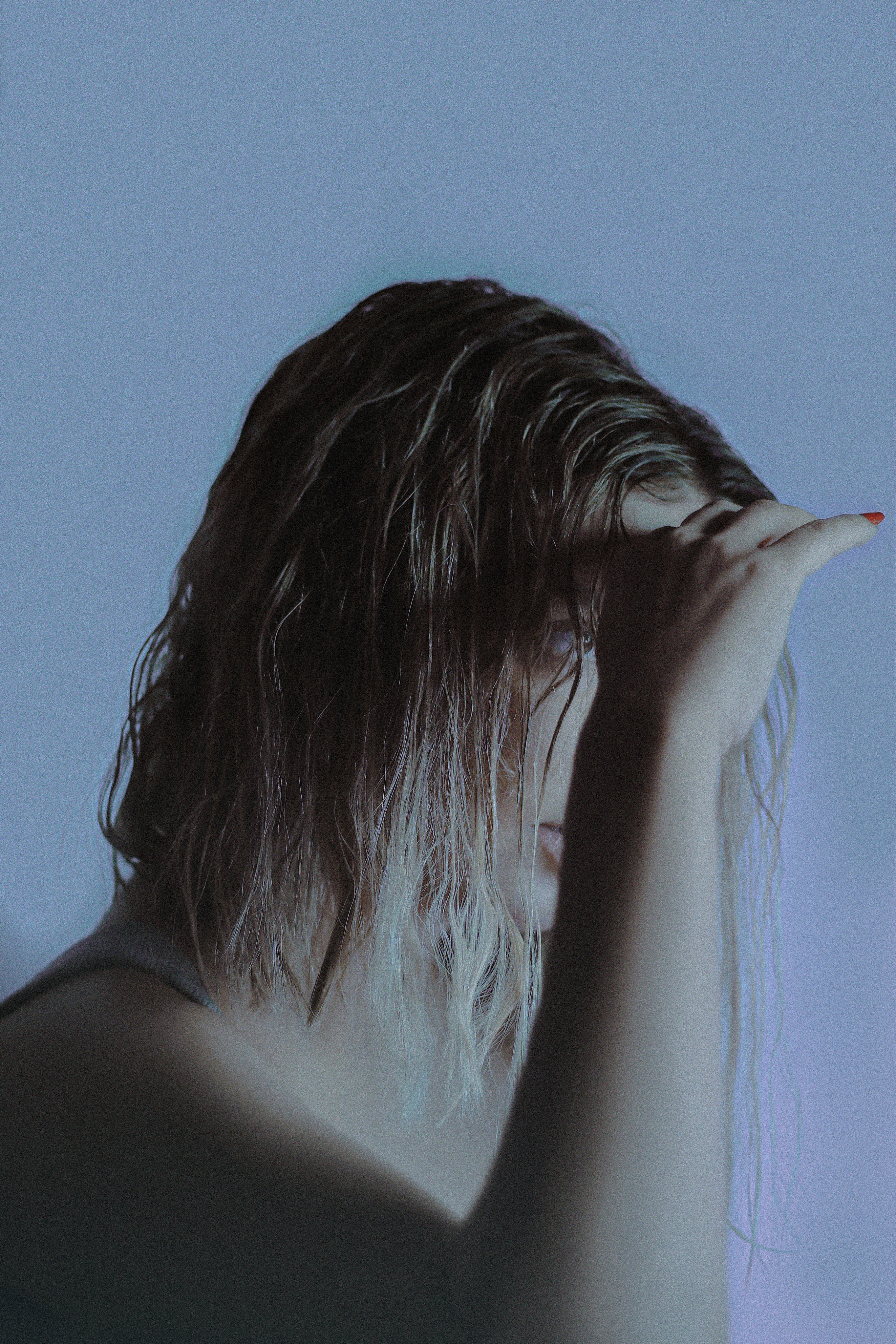 woman covering her face with her hair