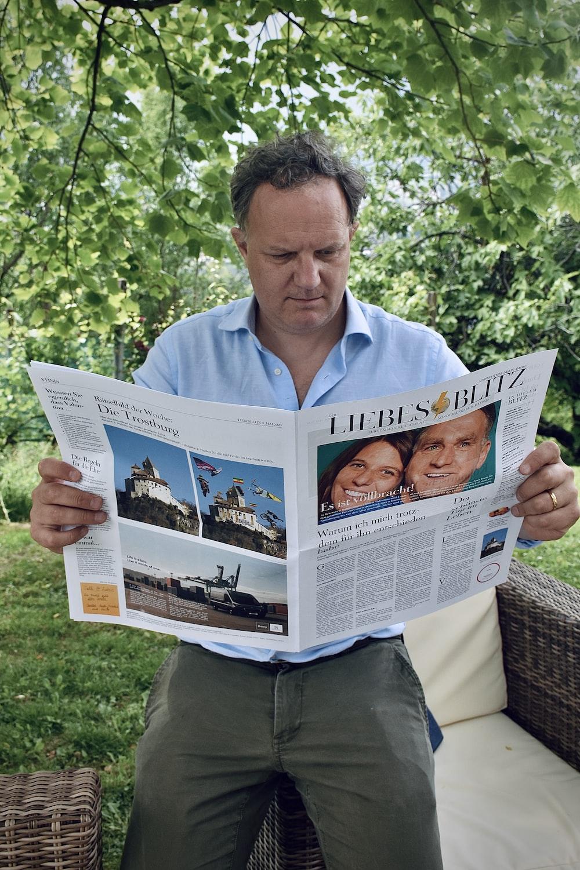 man in blue dress shirt holding newspaper
