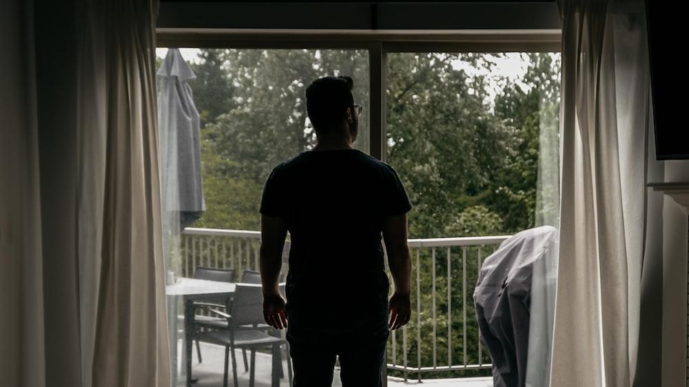 man in black crew neck t-shirt standing near white window curtain